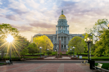 The Colorado State Capital Building with a sun burst and clouds